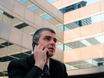 Phone discussion. Businessman speaking to the phone in the front of an office building Royalty Free Stock Images