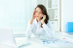 Phone discussion. Business woman talking on the phone with a troubled look on her face Royalty Free Stock Image