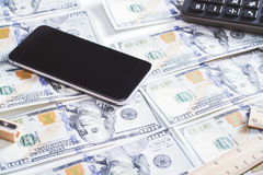 Phone on dollars. Blank smartphone and calculator placed on dollar banknotes. Mock up Stock Photo
