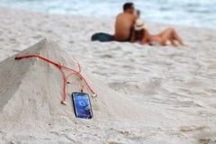 Phone and earphone on the sand on the beach Stock Photos