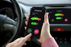 Phone in eco electric car touch multimedia system charging battery. Women hand holding phone in eco electric car touch multimedia system with charging battery on royalty free stock photos