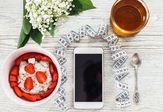 Mobile phone fitness application and light breakfast Stock Photography