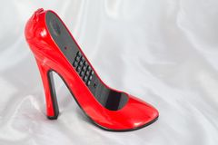 Phone in the form of red female high-heeled shoes. The stylish phone in the form of red female high-heeled shoes on the satin cloth stock photos