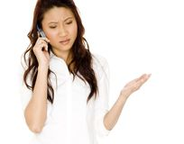 Phone Frustration. A young asian woman looks frustrated by her phone call Royalty Free Stock Photography