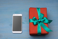 Phone and a gift on the table Stock Image