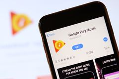 Phone with Google Play Music icon on screen close up with blur website on laptop. Los Angeles, California, USA - 30 November 2019