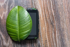 Phone on the green leaf of a plant. Phone on a green leaf on wooden background Stock Images