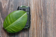 Phone on the green leaf of a plant. Phone on a green leaf on wooden background Royalty Free Stock Image