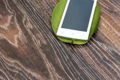 Phone on the green leaf of a plant. Phone on a green leaf on wooden background Royalty Free Stock Photos