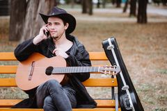Phone and guitar. Young man speaking phone on the bench in the park royalty free stock photography