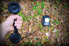 Phone in hand. Old black rotary phone on autumn leaves Stock Images