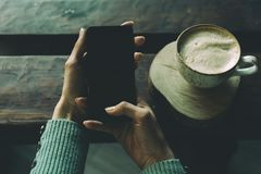 Phone in hand and a cup of coffee on the table stock photo