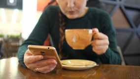 Phone in the hand of the girl in focus, woman is drinking coffee on the blurred background stock video footage