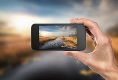 Phone in hand and landscape Royalty Free Stock Images