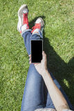 Phone in hand legged on grass Stock Photo
