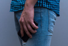 Phone in hand lowered. The man in jeans and a plaid shirt. Royalty Free Stock Image