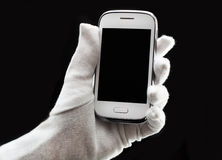 Phone in hand. Smart phone in hand, glove, black background Royalty Free Stock Photography