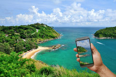 Phone on hand to follow beautiful travel location from internet, Royalty Free Stock Photography