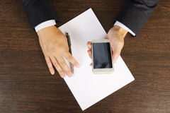 Phone in hands of a businessman on the desktop close-up, top view. Royalty Free Stock Image
