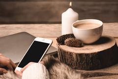 Phone in the hands of the girl, a white cup with coffee, candle and cones stock photos