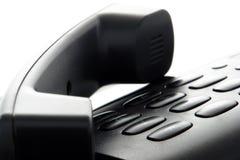 Phone Handset on Hold over Slick Telephone Keypad. Black phone handset resting on office desk slick telephone keypad while placing a call on hold Stock Image