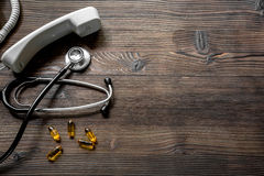 Phone handset, pills and phonendoscope on dark wooden desk top view make appointment with a doctor space for text Stock Images