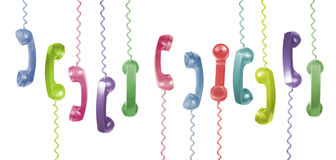 Phone Handsets. Lots of different coloured old phone handsets are hanging on white background Royalty Free Stock Photography