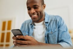 Inspired young man sending messages. Phone. Handsome gleeful young afro-american man smiling and writing a message on his phone and looking at the screen Royalty Free Stock Image