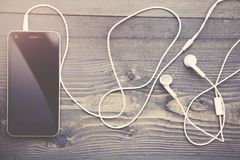 Phone and headphones. Cell phone and headphones on wooden table Royalty Free Stock Images