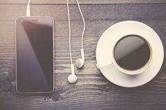 Phone, headphones and coffee. On wooden table Stock Images