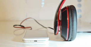 Phone with headphones. Nwhite phone photo with black and red headphones Royalty Free Stock Images