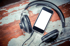 Phone and headphones over wooden background music Royalty Free Stock Photos
