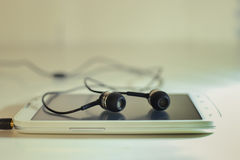 Phone with headphones. Photos of black headphones on a white phone Stock Images