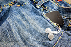 Phone and headphones in the pocket jean Royalty Free Stock Image