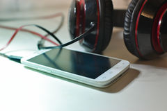 Phone with headphones. White phone photo with black and red headphones Royalty Free Stock Image