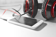 Phone with headphones. White phone photo with black and red headphones Royalty Free Stock Photo