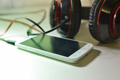Phone with headphones. White phone photo with black and red headphones Stock Image