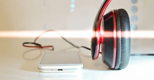 Phone with headphones. White phone photo with black and red headphones Royalty Free Stock Photography