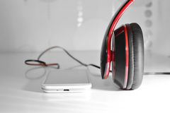 Phone with headphones. White phone photo with black and red headphones Stock Images