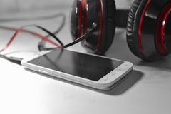 Phone with headphones. White phone photo with black and red headphones Royalty Free Stock Images