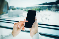 Phone holding in female hand on the blured Stock Image