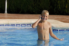 Phone-home 5. Young wet boy making a phone call in a swimming pool stock photography
