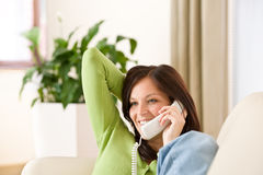 On the phone home: Happy woman calling Stock Images