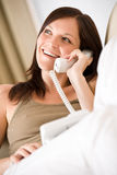 On the phone home: Smiling woman calling. Looking up royalty free stock image