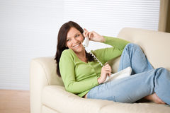 On the phone home: Smiling woman calling Royalty Free Stock Image