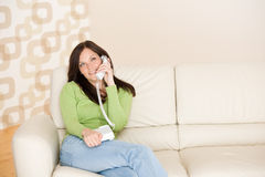 On the phone home: Smiling woman calling Royalty Free Stock Photos