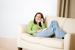 On the phone home: Smiling woman calling Royalty Free Stock Photo