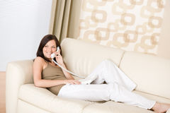 On the phone home - Smiling woman on sofa calling Stock Photos