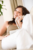 On the phone home: Young woman calling in lounge Stock Images