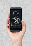 Phone with icon businessman. Phone with businessman icon  in hand on gray background Stock Photos
